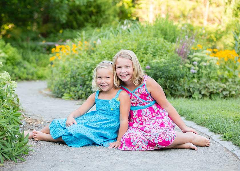 two girls sitting in garden path