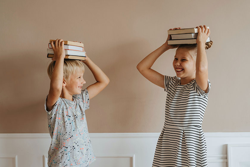laughing children holding books on their heads