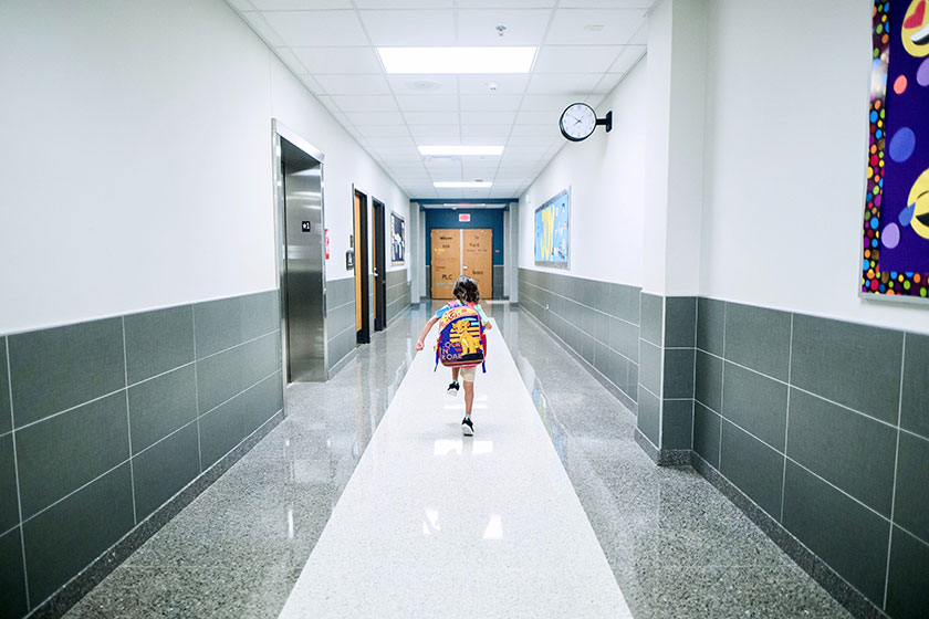 child with backpack in empty school hallway