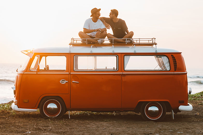 two guys sitting atop a retro camper bus