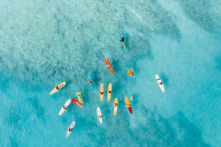 overhead photo of people on surfboards and floats in tropical water